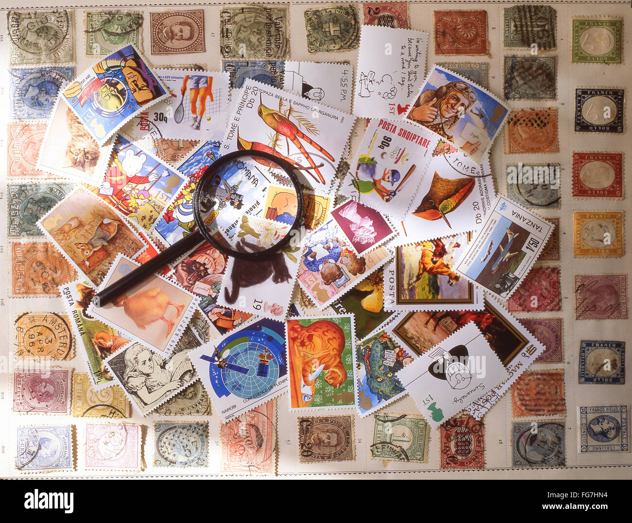 Collection of stamps with magnifying glass in studio setting, Berkshire, England, United Kingdom - Stock Image