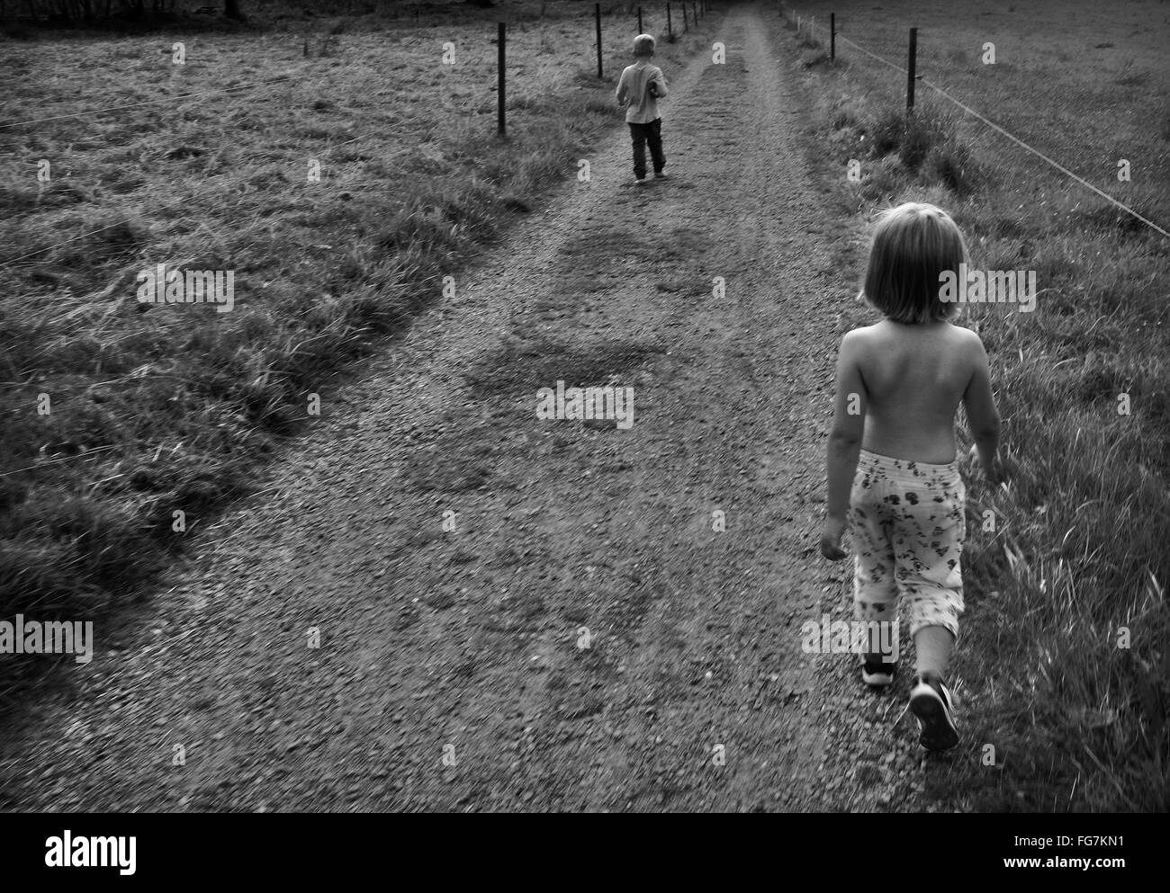 Rear View Of Siblings Walking On Country Road - Stock Image