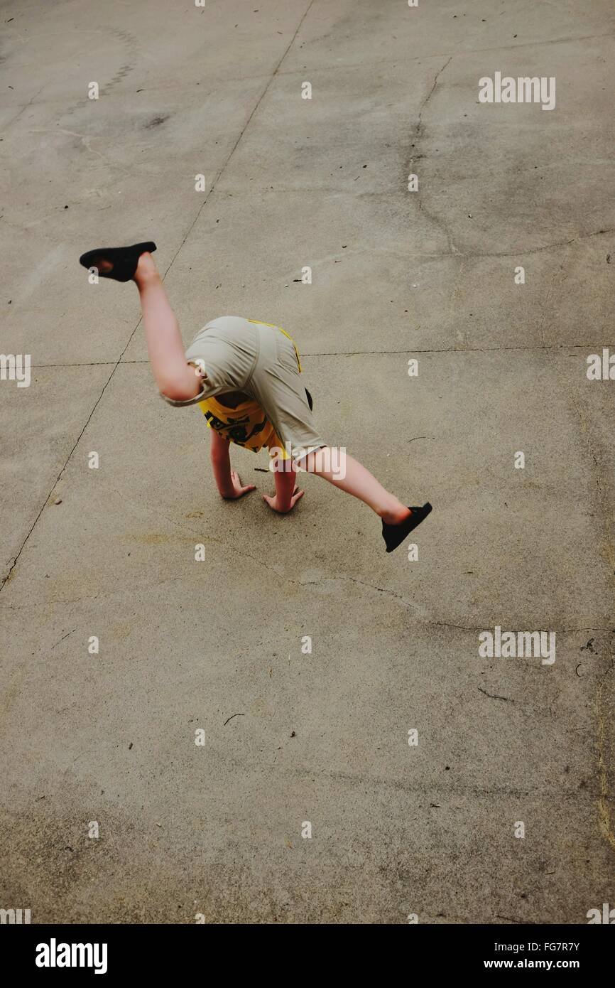 High Angle View Of Boy Performing Handstand On Street - Stock Image
