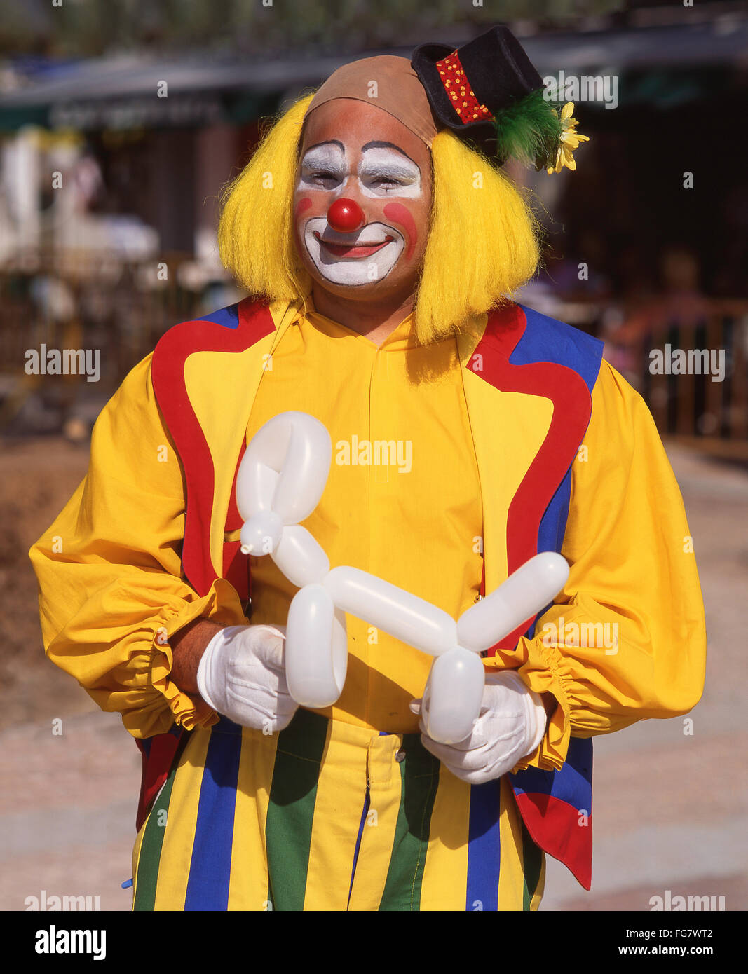 Colourful clown holding modeled balloon, Berkshire, England, United Kingdom - Stock Image