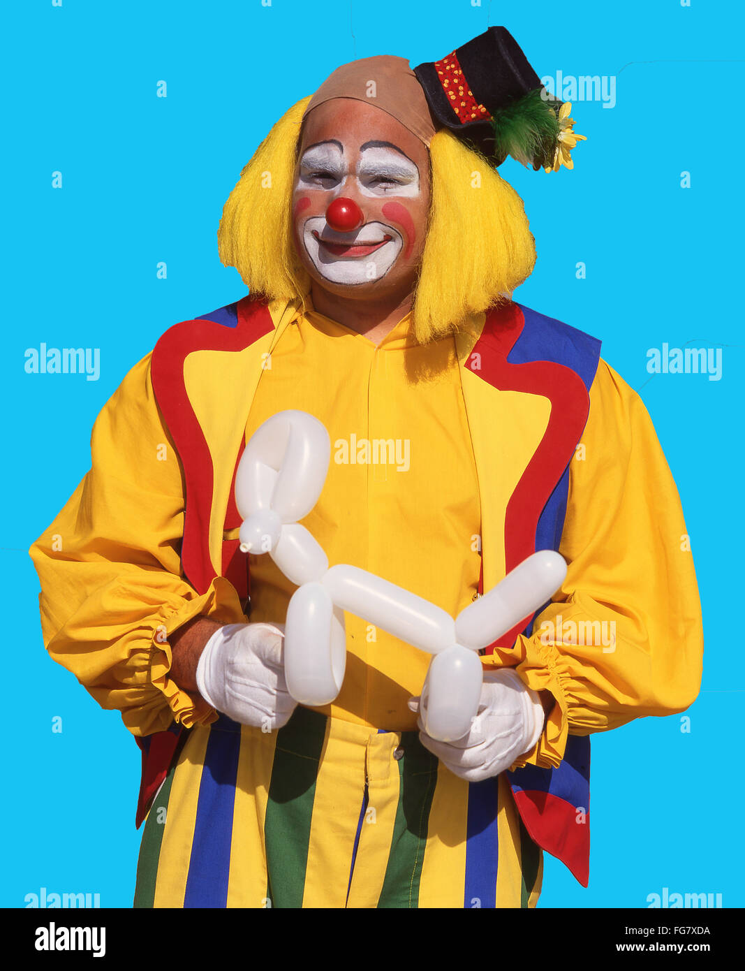Colourful clown holding modelled balloon, Berkshire, England, United Kingdom - Stock Image