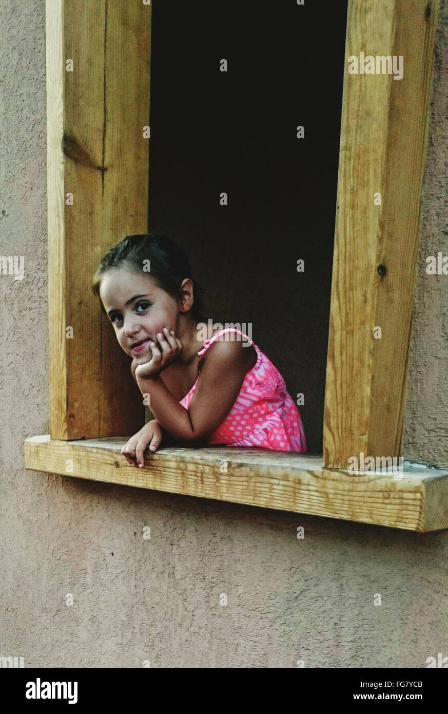Portrait Of Girl With Hand On Chin Looking Through Window - Stock Image