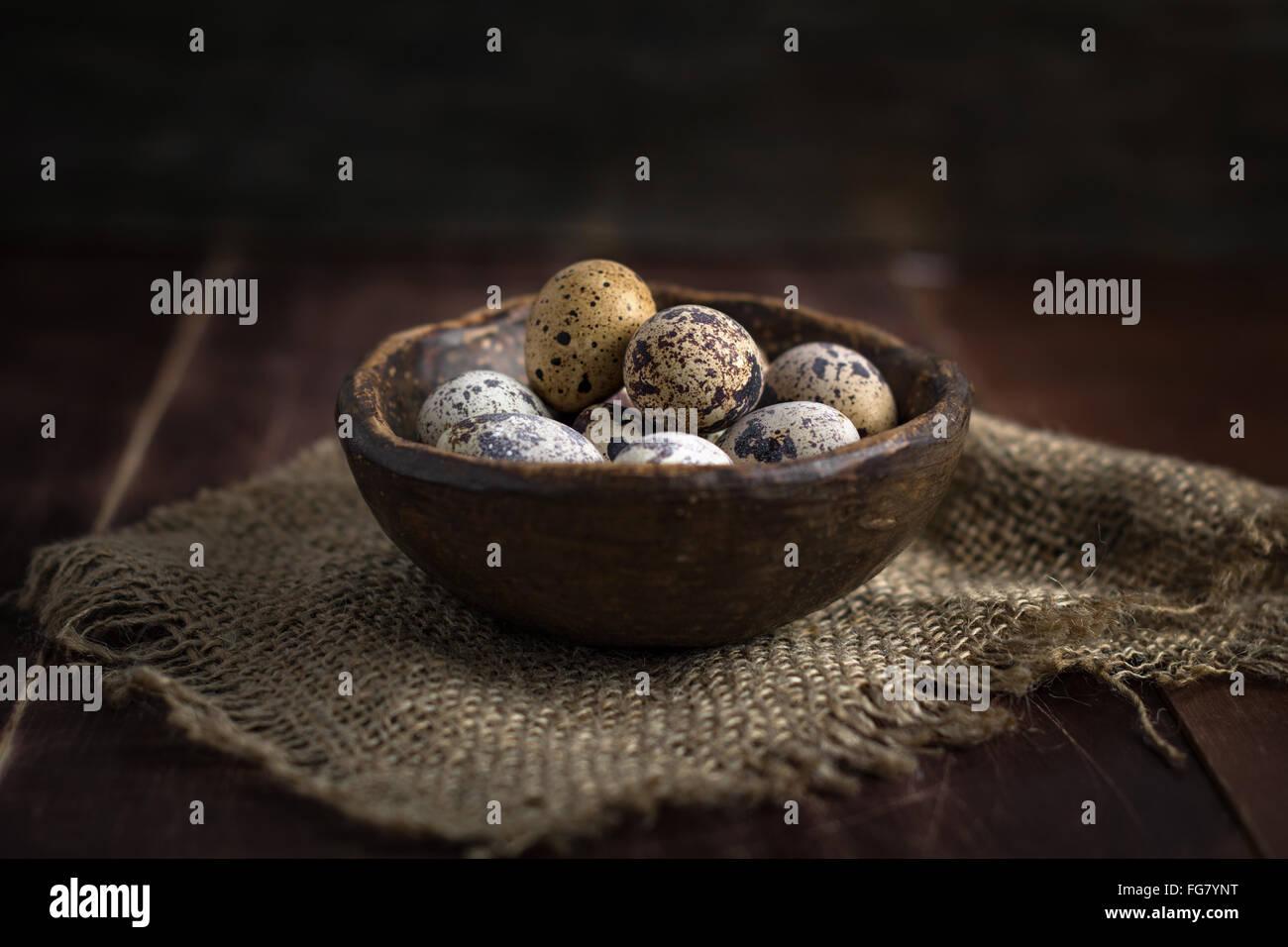 Fresh organic quail eggs in ceramic bowl on linen rag. Natural light, selective focus - Stock Image