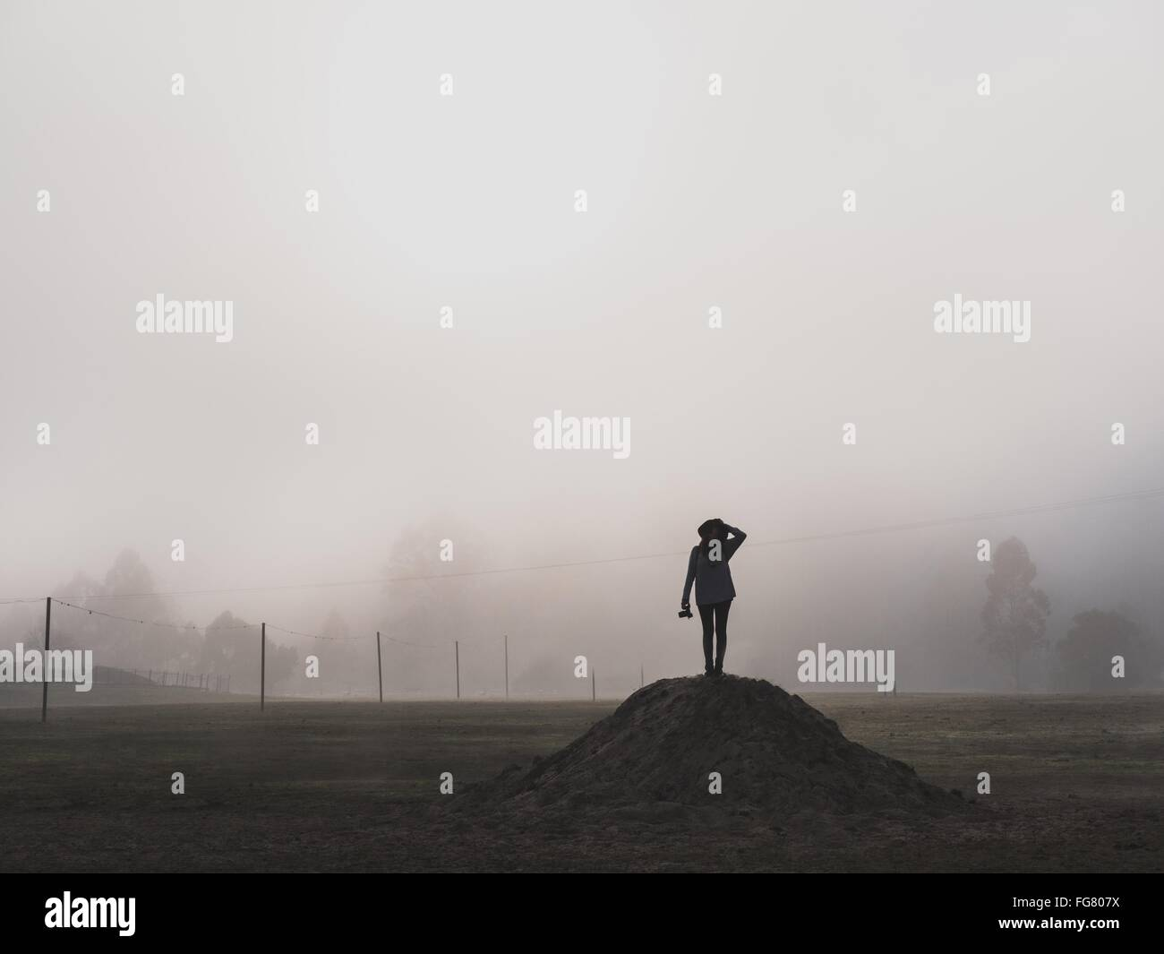 Silhouette Woman Standing On Heap In Foggy Weather - Stock Image