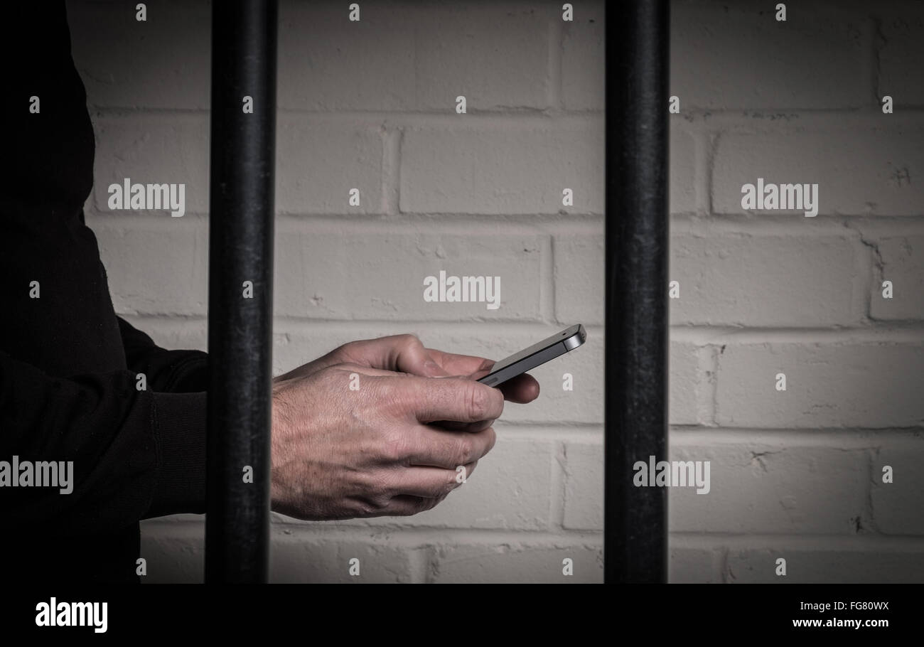 A prisoner in prison using a mobile phone behind bars in a cell - Stock Image