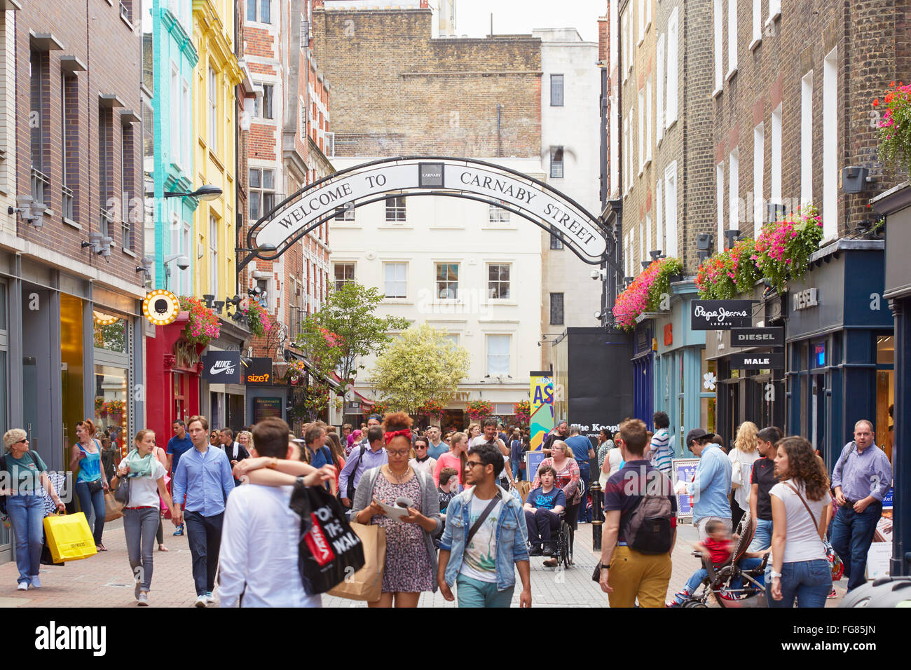 Carnaby street, famous shopping street with people in London - Stock Image