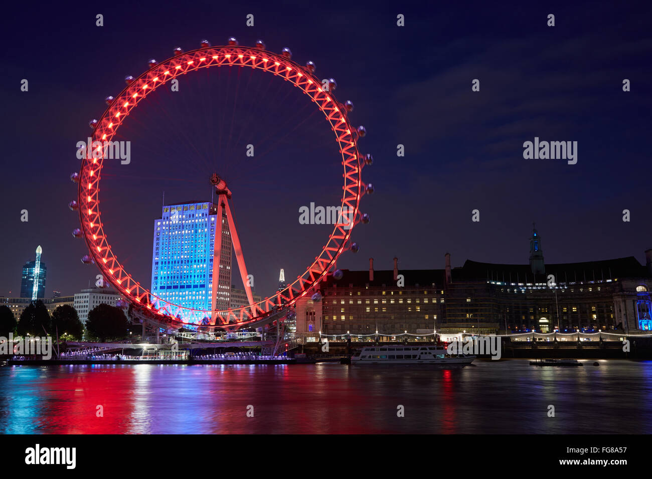 London eye, ferris wheel, illuminated in red in the night, reflection in Thames river in London - Stock Image