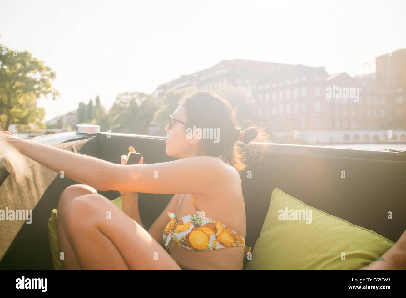 Woman Sitting And Enjoying In Boat At River - Stock Image