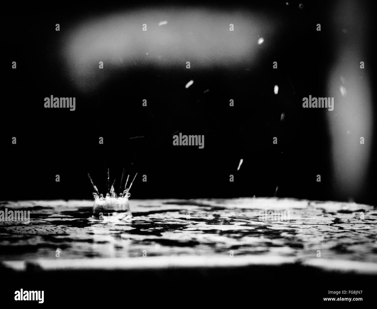 Close-Up Of Splashing Droplet On Puddle - Stock Image