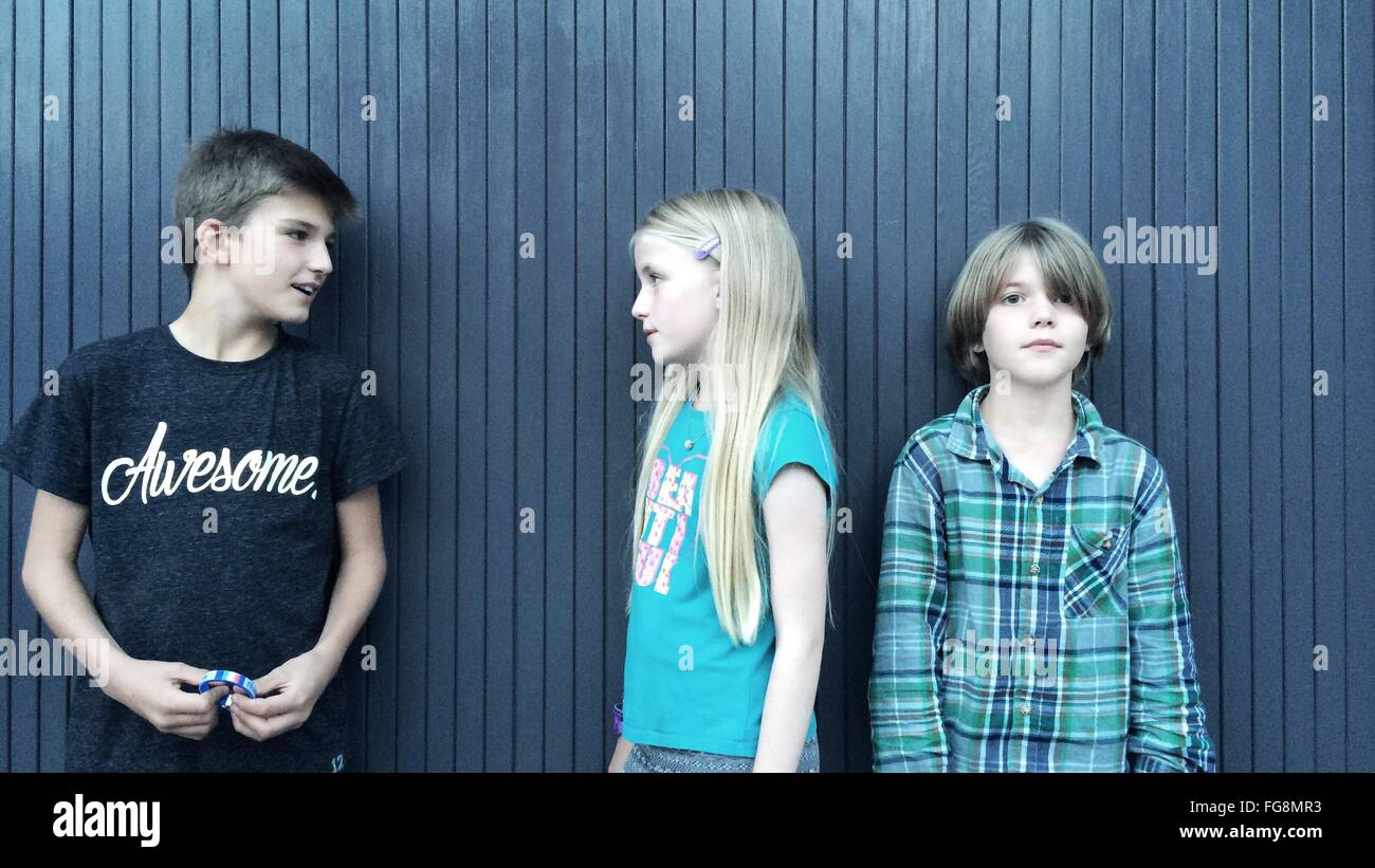 Siblings Standing Against Patterned Wall - Stock Image