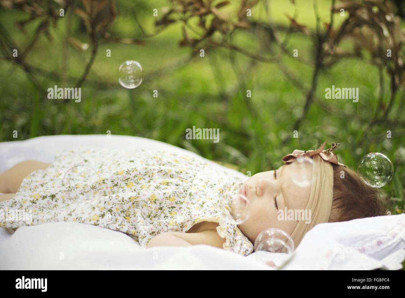 Baby Girl Surrounded By Bubbles In Park - Stock Image
