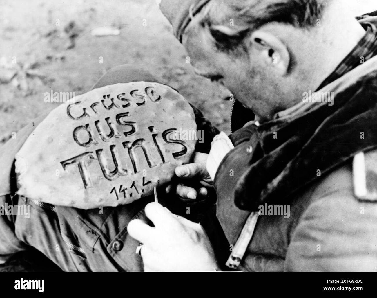 The Nazi propaganda picture shows a soldier of the German Wehrmacht crafting a greeting board with the words 'Gruesse - Stock Image