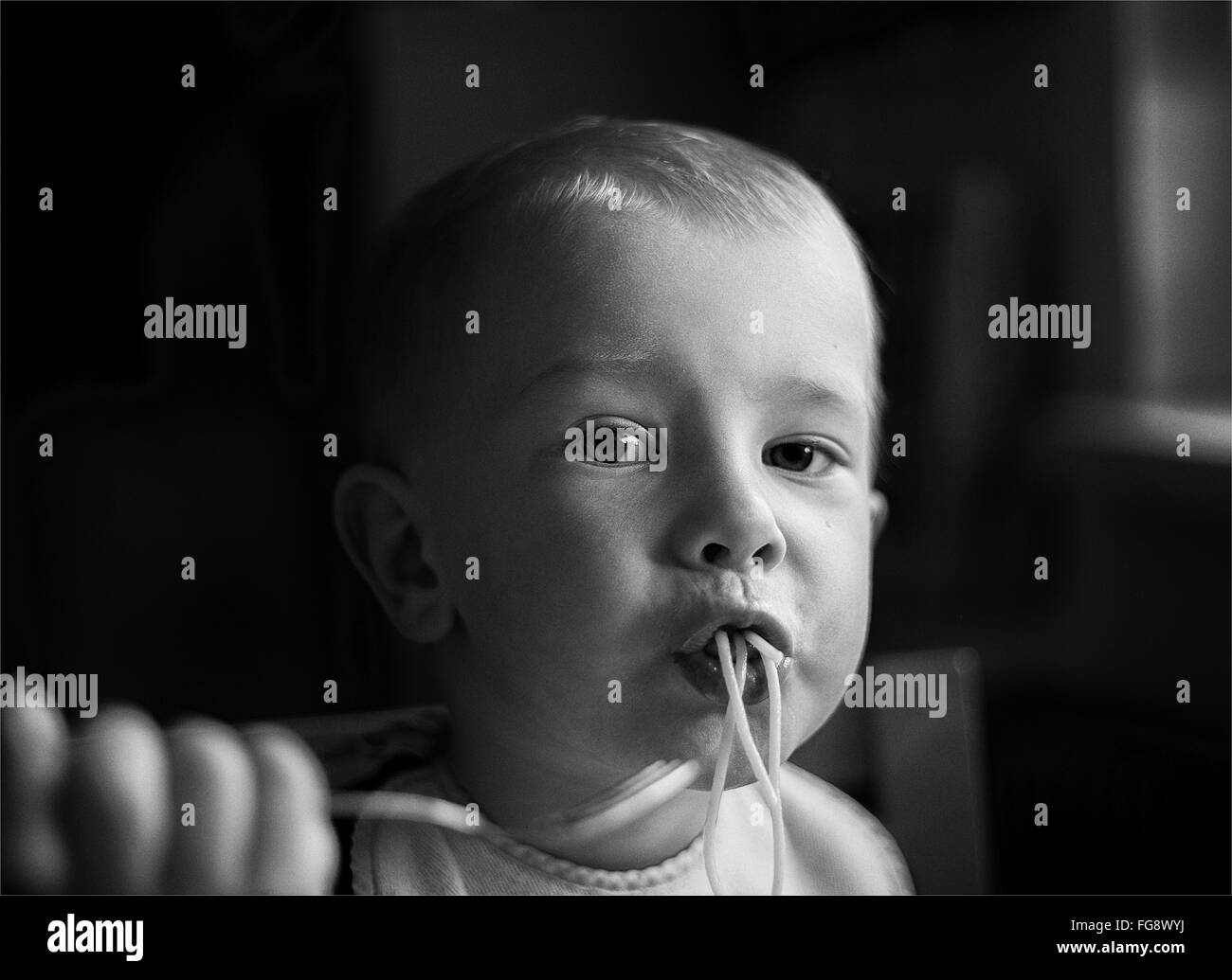 Portrait Of Boy Eating Noodles At Home - Stock Image