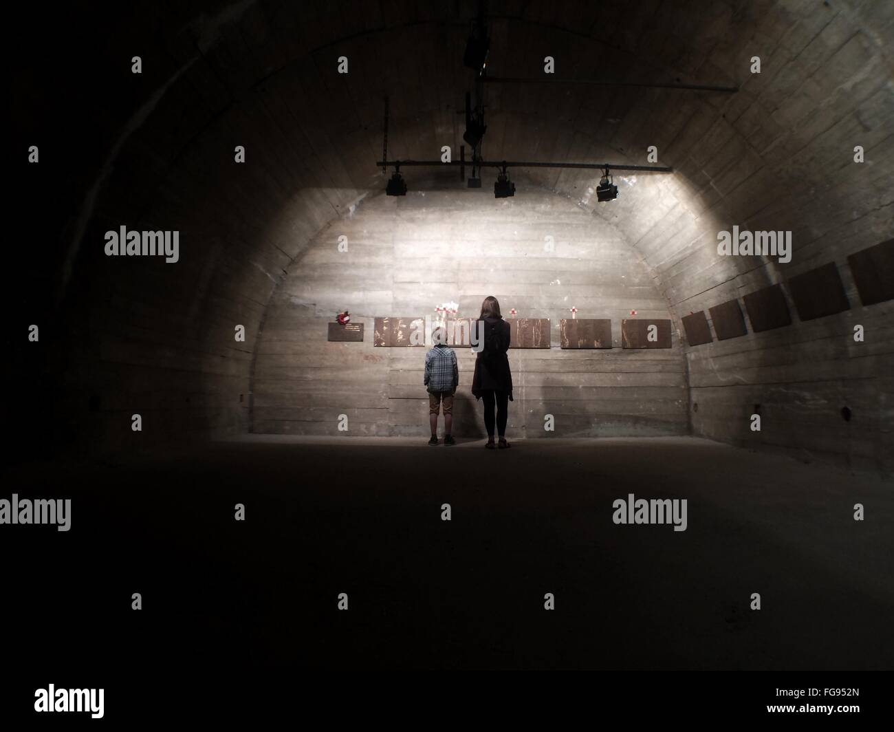 Rear View Of Mother And Son Standing Against Wall In Old Building - Stock Image