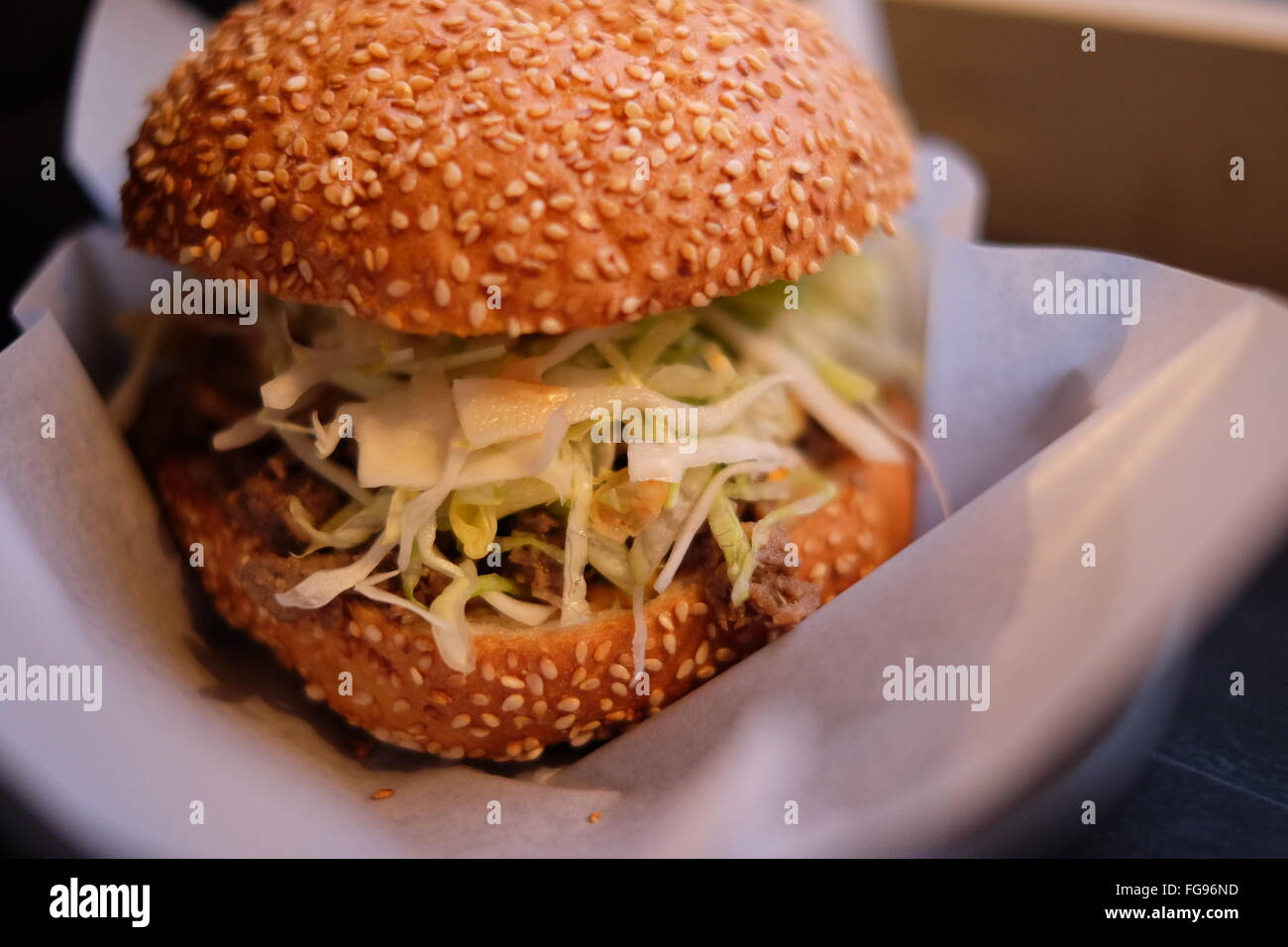 Close-Up Of Burger On Tissue Paper - Stock Image