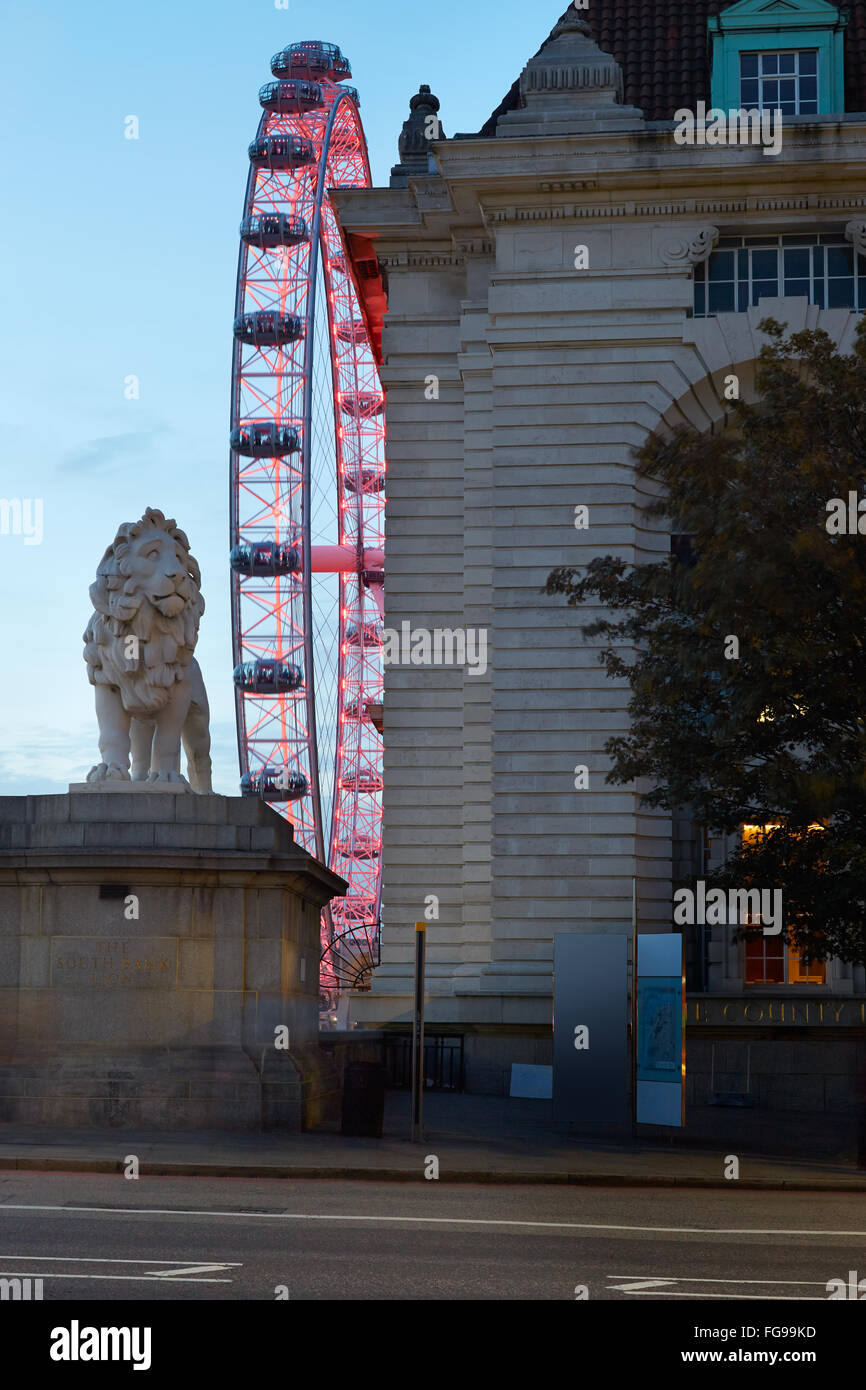 London eye, ferris wheel, illuminated in red in the night and lion statue in London - Stock Image