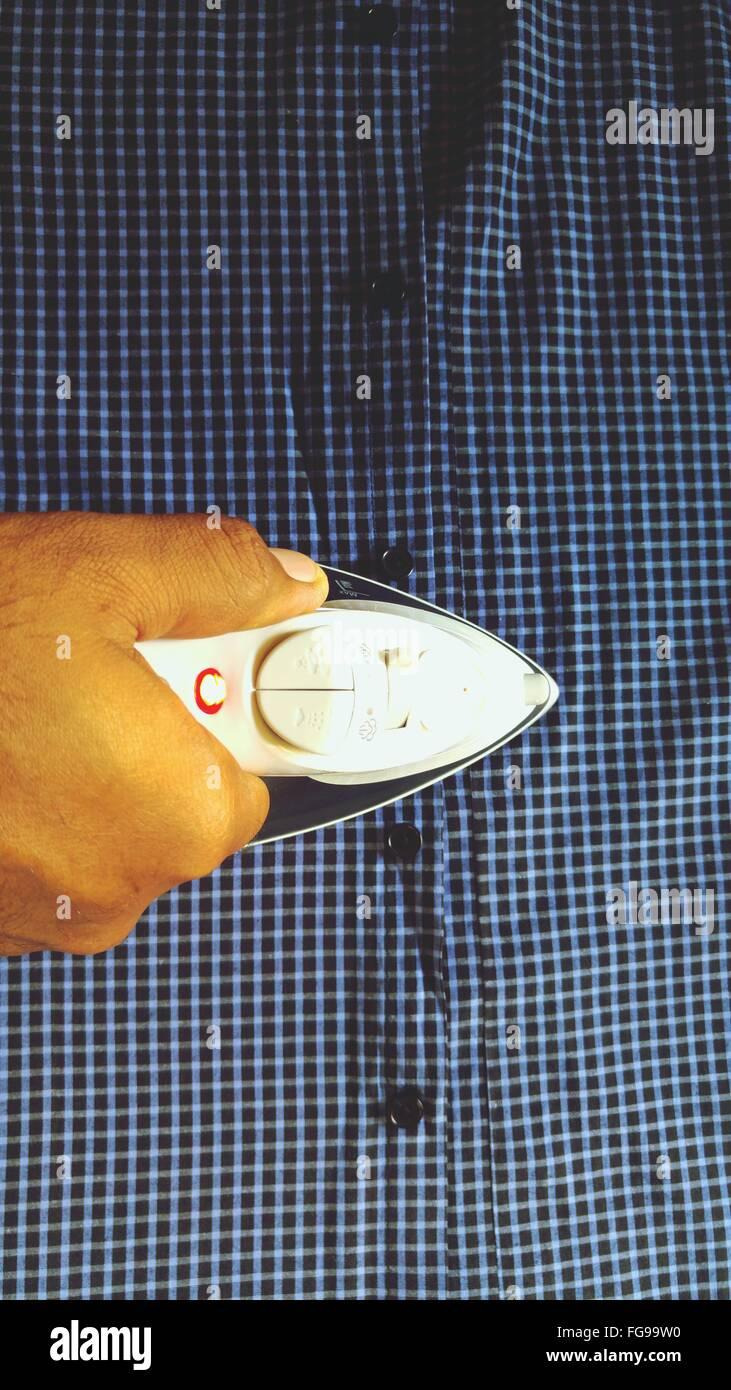 Cropped Image Of Hand Ironing Shirt - Stock Image