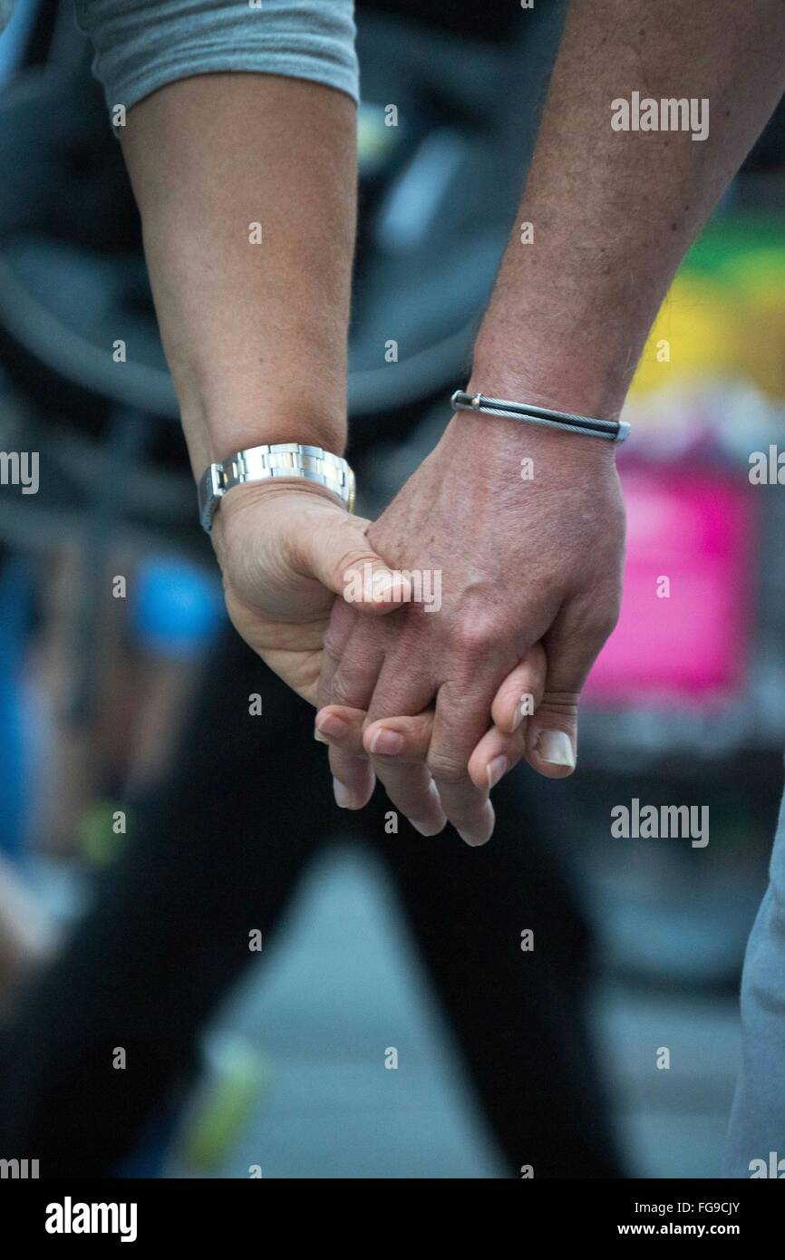 Cropped Image Of Couple Holding Hands - Stock Image
