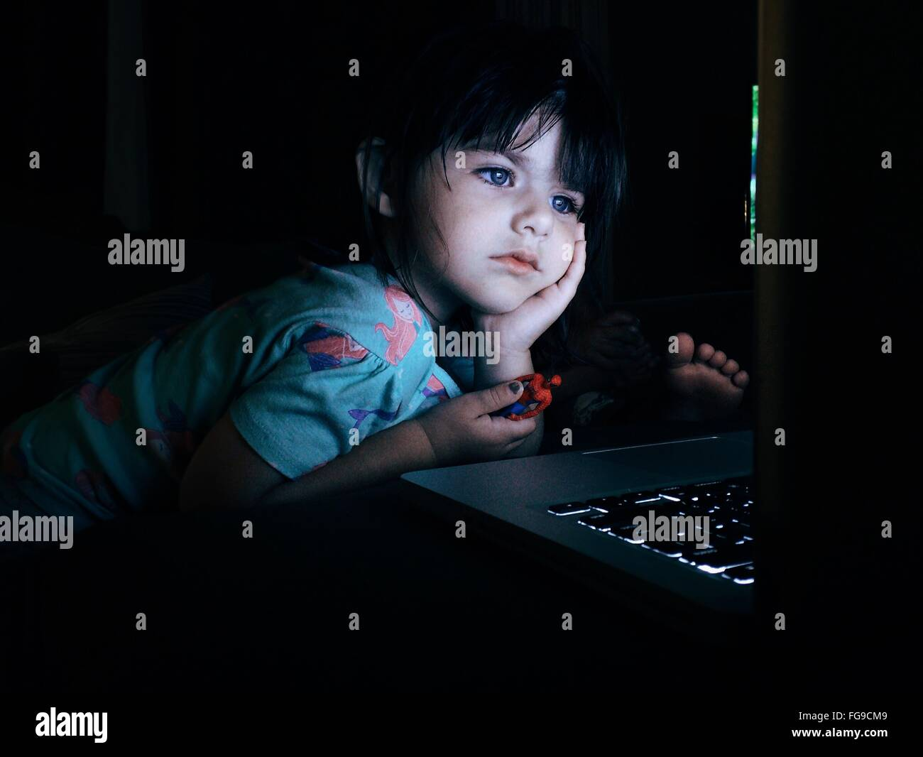 Girl With Hand On Chin Looking At Laptop - Stock Image