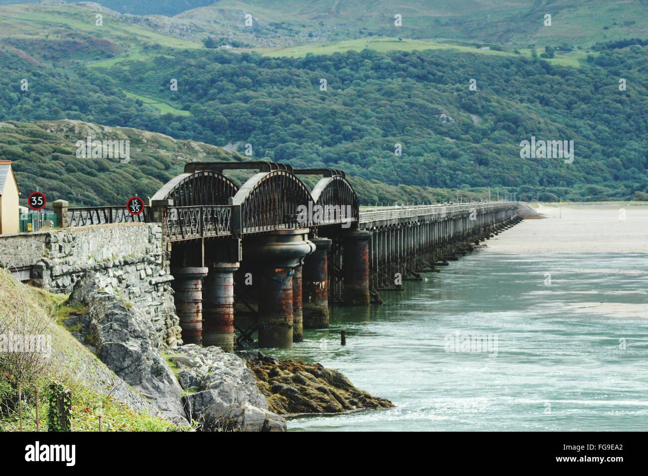 Barmouth Bridge Over River Mawddach Against Green Landscape In Snowdonia Stock Photo