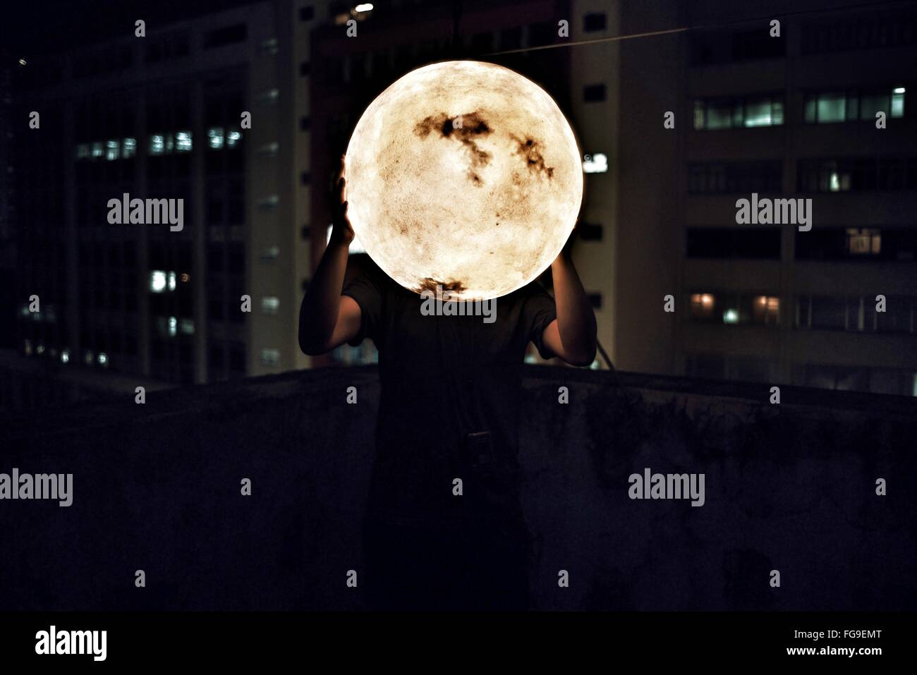 Man Holding Artificial Moon At Night - Stock Image