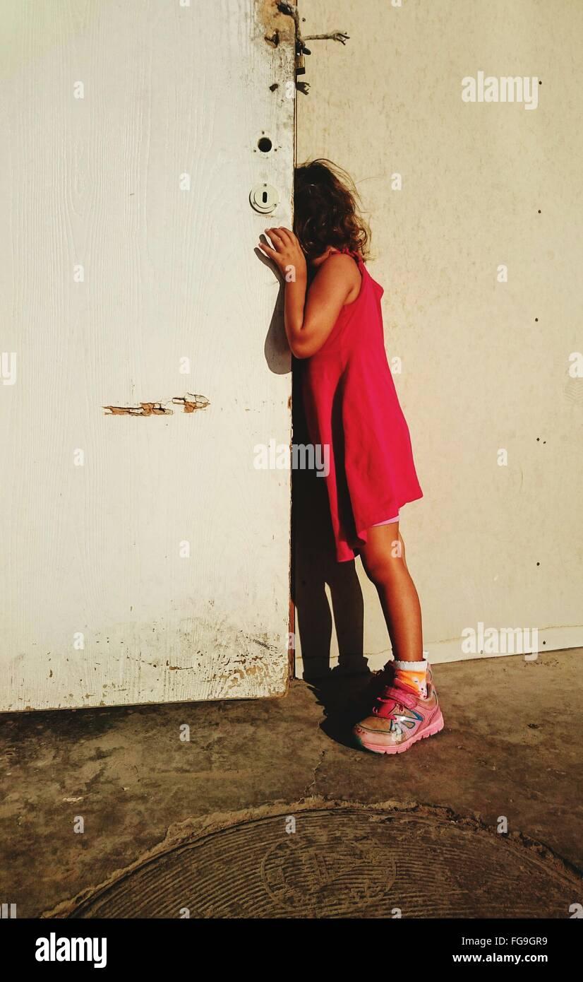 Side View Of Girl Peeking From Door - Stock Image