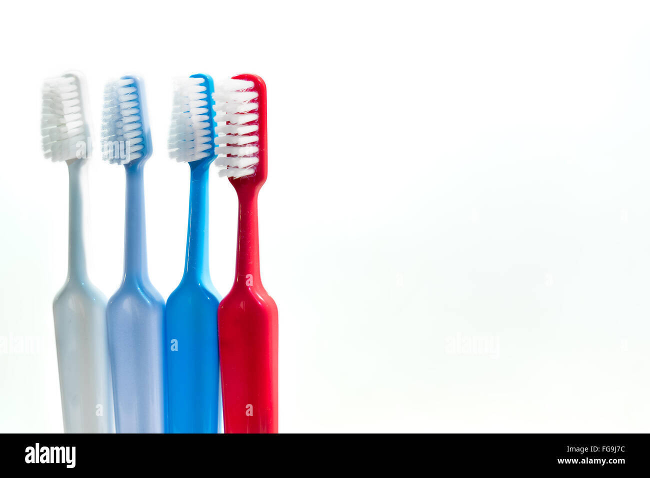 Close-Up Of Multi Colored Toothbrushes Against White Background - Stock Image