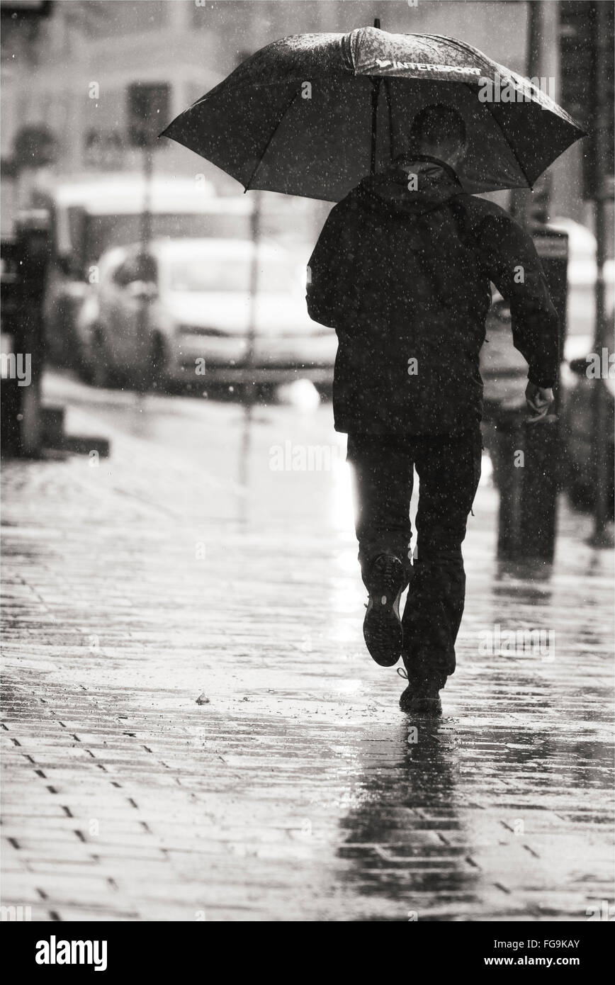 Rear View Of Man Holding Umbrella Running On Street During Rainy Stock Photo Alamy