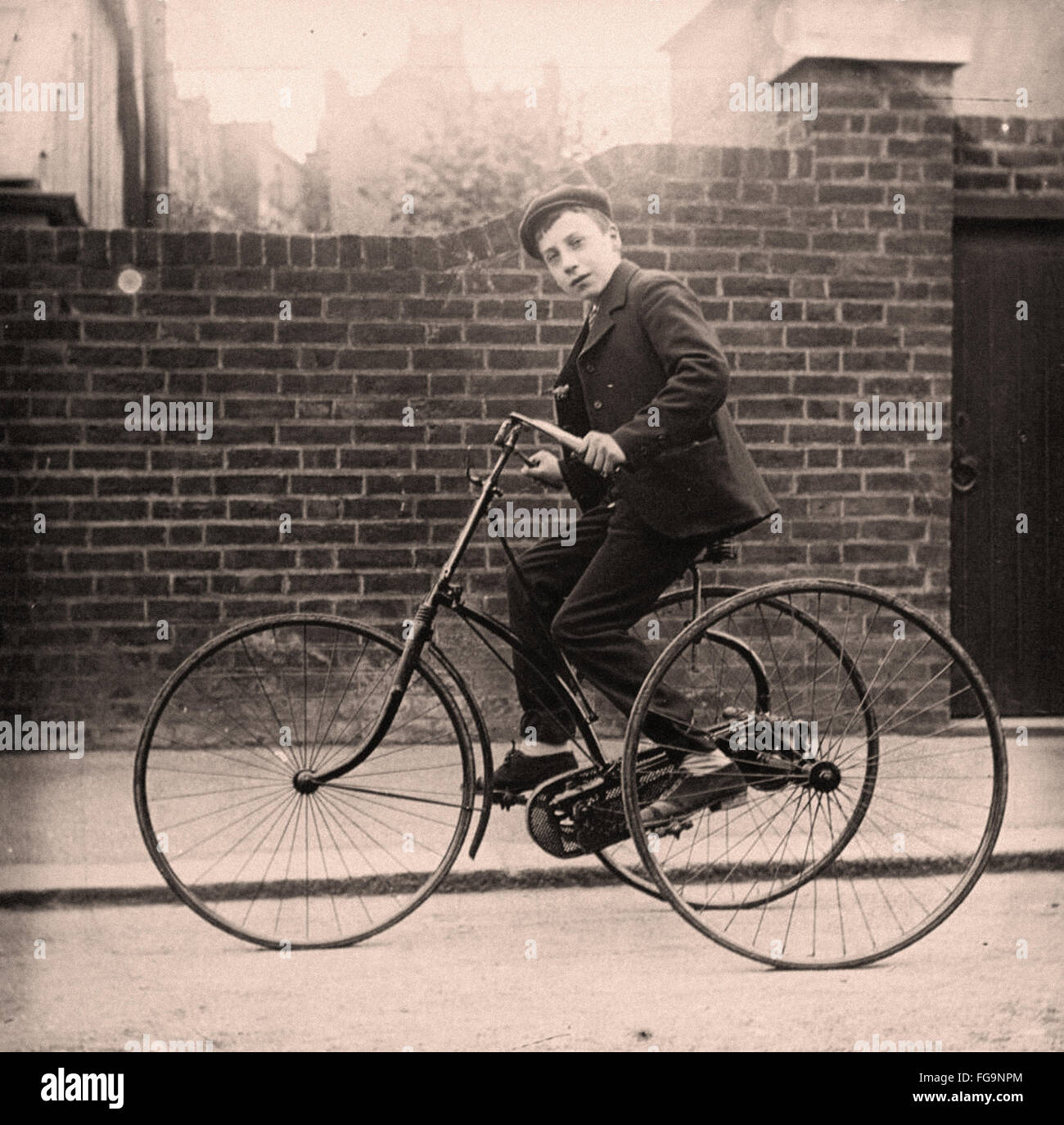 Young lad on an early tricycle - 1890 - Stock Image