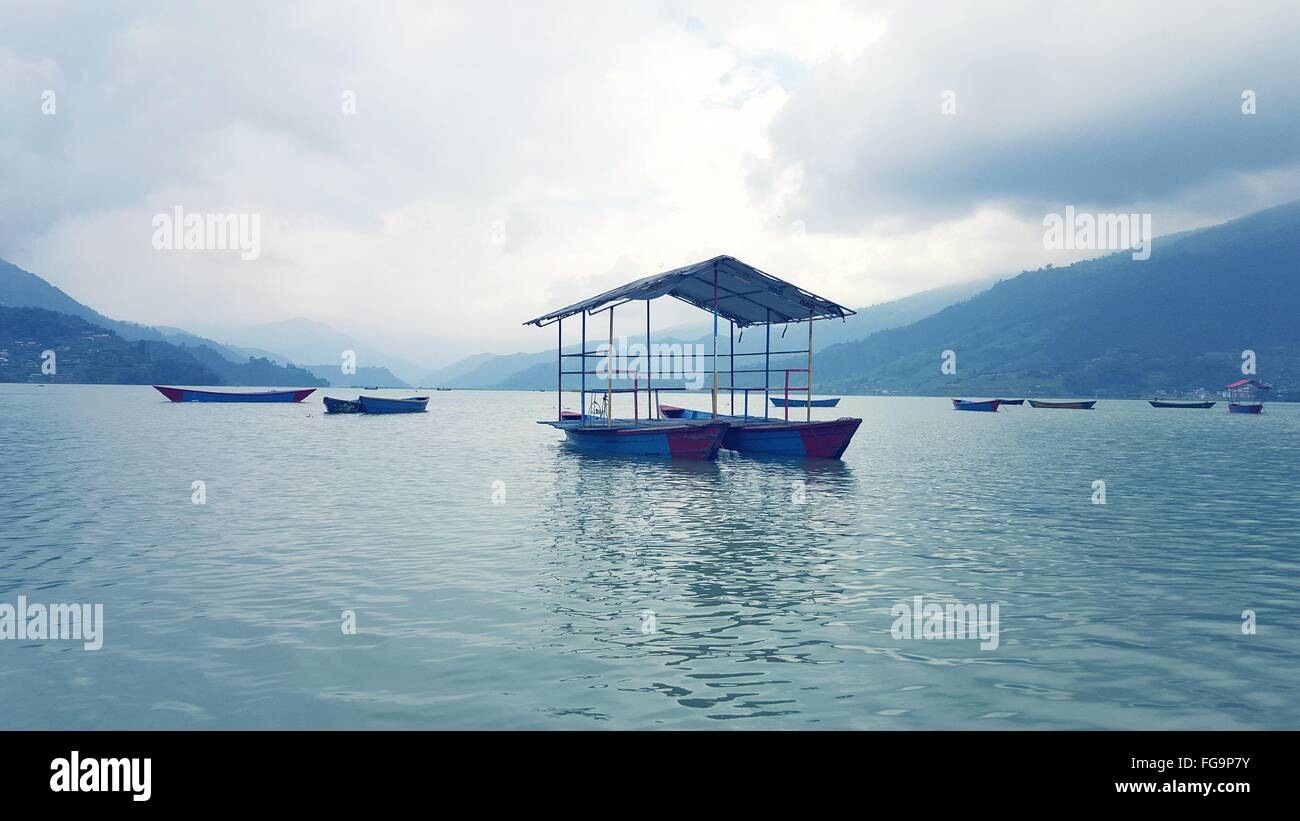 Boats In Phewa Lake Against Cloudy Sky - Stock Image