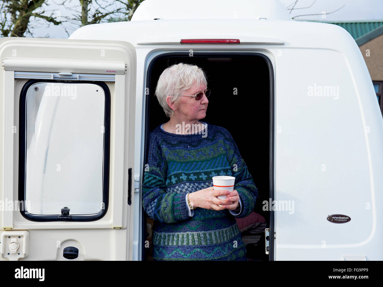 Senior woman at the door of her Romahome Duo, a small motorhome, England UK - Stock Image