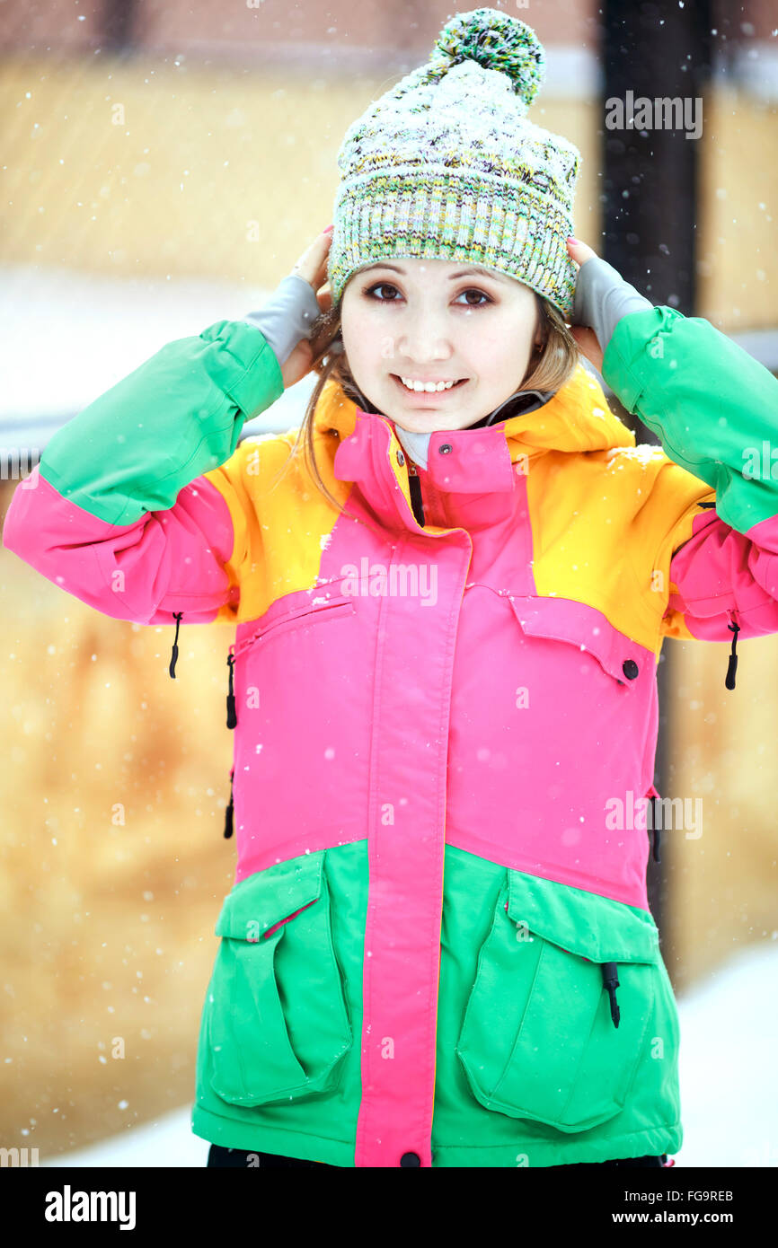 Pretty positive girl in bright colorful ski suit winter outdoors, outside during snowfall. - Stock Image
