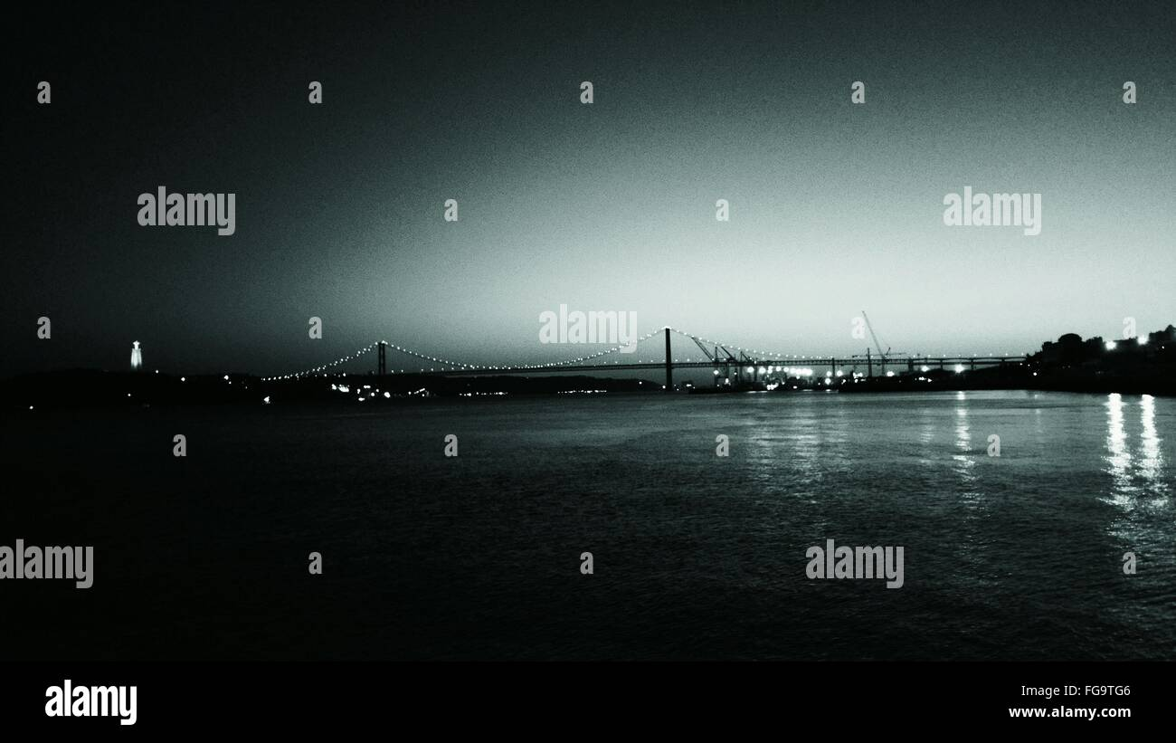 Distant View Of April 25Th Bridge Over Tagus River At Night Stock Photo
