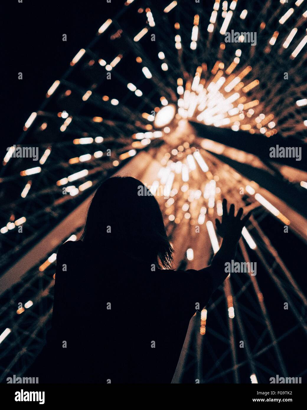 Low Angle View Of Silhouette Girl Against Illuminated Ferris Wheel At Night In Amusement Park Stock Photo