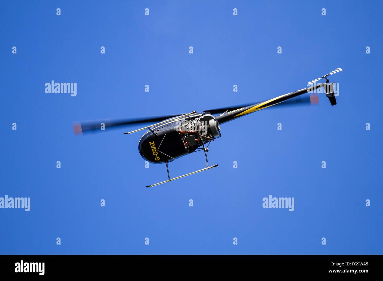 Robinson R22 G-OSAZ is a two-bladed single-engine light utility helicopter flying overhead near the airport in Dundee, - Stock Image