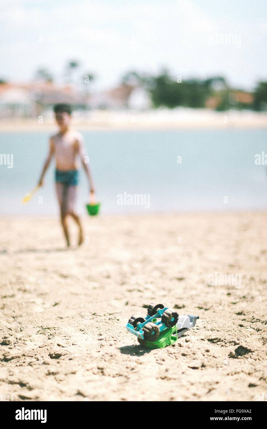 Boy Playing On Beach With Toys - Stock Image