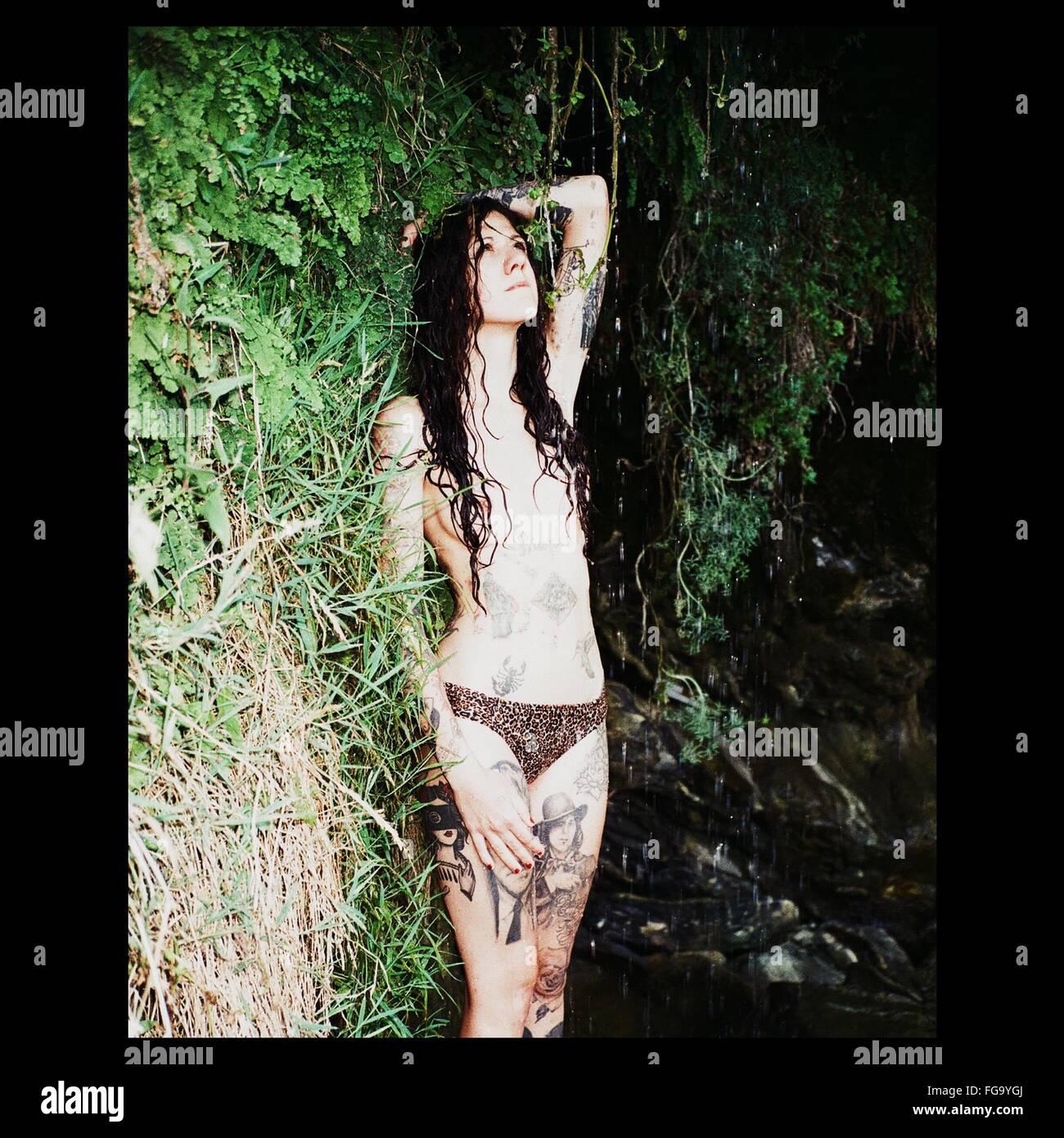 Tattooed Woman In Bikini Bottom Standing In Cave On Rainy Day - Stock Image