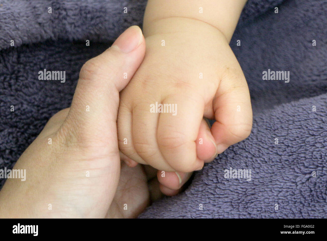Close-Up Of Baby Holding Mother Hand - Stock Image