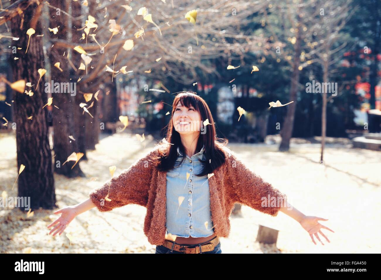Happy Young Woman With Arms Outstretched In Park - Stock Image