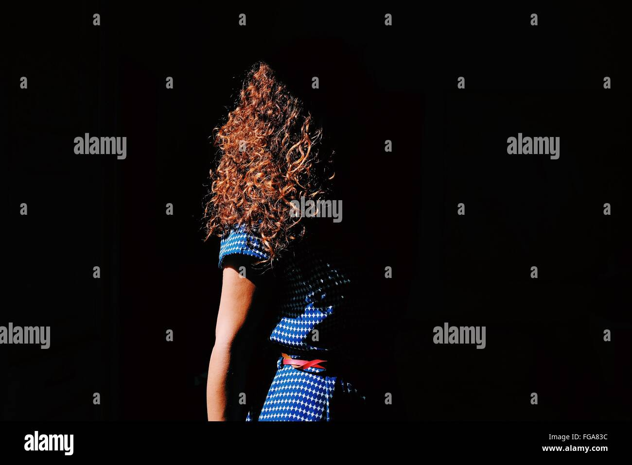 Brown Curly Hair Woman In Sunlight - Stock Image