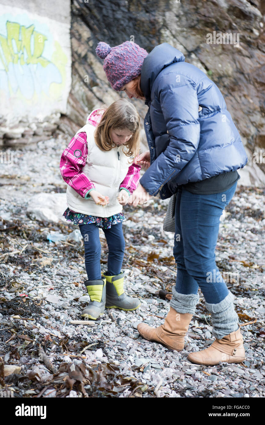 Middle-class white mum and young daughter on a beach in winter looking for shells, pebbles and Mermaid rings Stock Photo