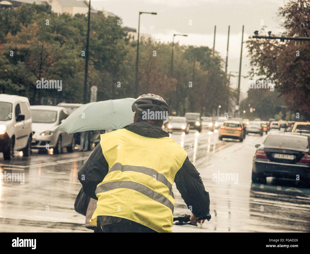 Rear View Of Man In Reflective Clothing Cycling On Wet City Street - Stock Image