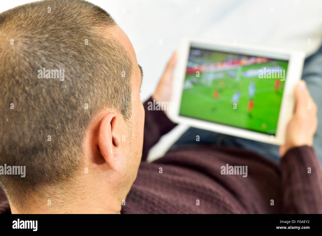 a young man lying on the couch watches a soccer match in streaming in his tablet computer - Stock Image