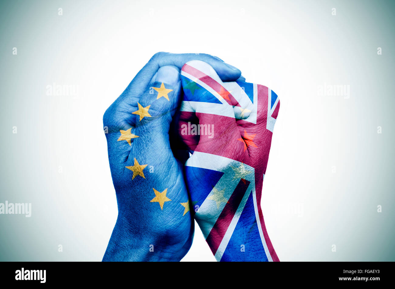 hand patterned with the flag of the European Community envelops another hand patterned with the flag of the United Stock Photo