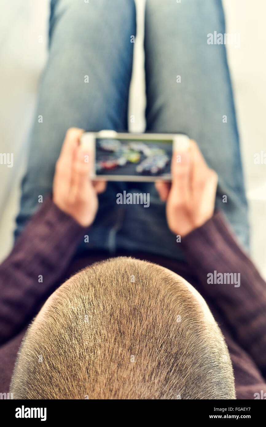 a young man lying on the couch watches a car race in streaming in his smartphone - Stock Image