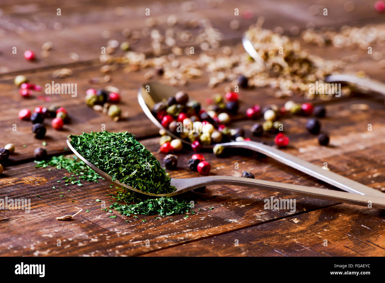 three spoons full of chopped dried parsley, peppercorns of different varieties and anise seeds on a rustic wooden - Stock Image