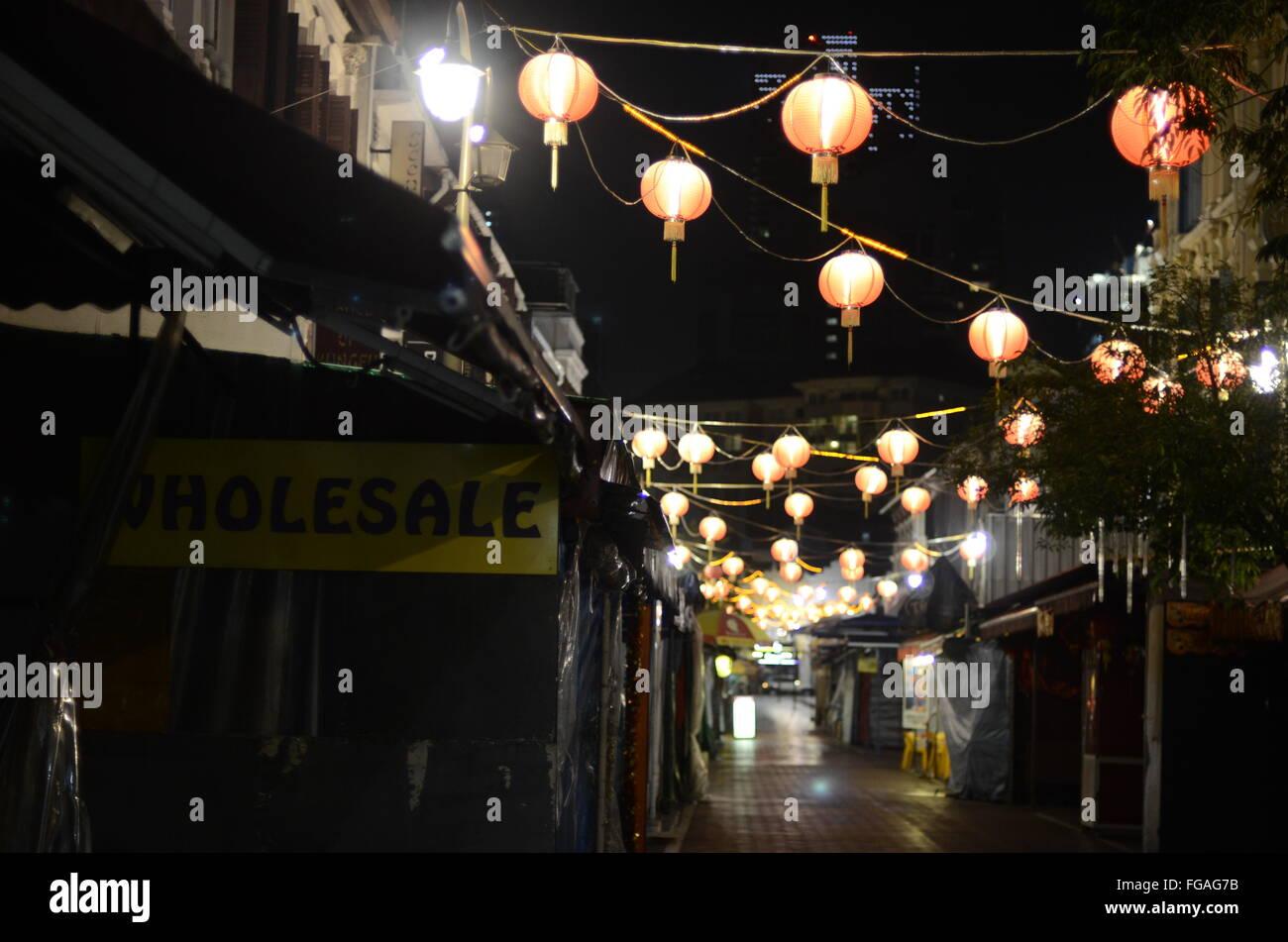 Illuminated Lanterns Hanging On Alley Amidst Market Stalls - Stock Image
