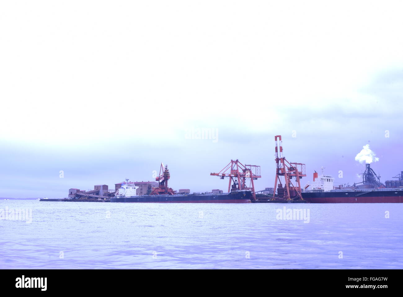 Sea By Commercial Dock Against Sky - Stock Image