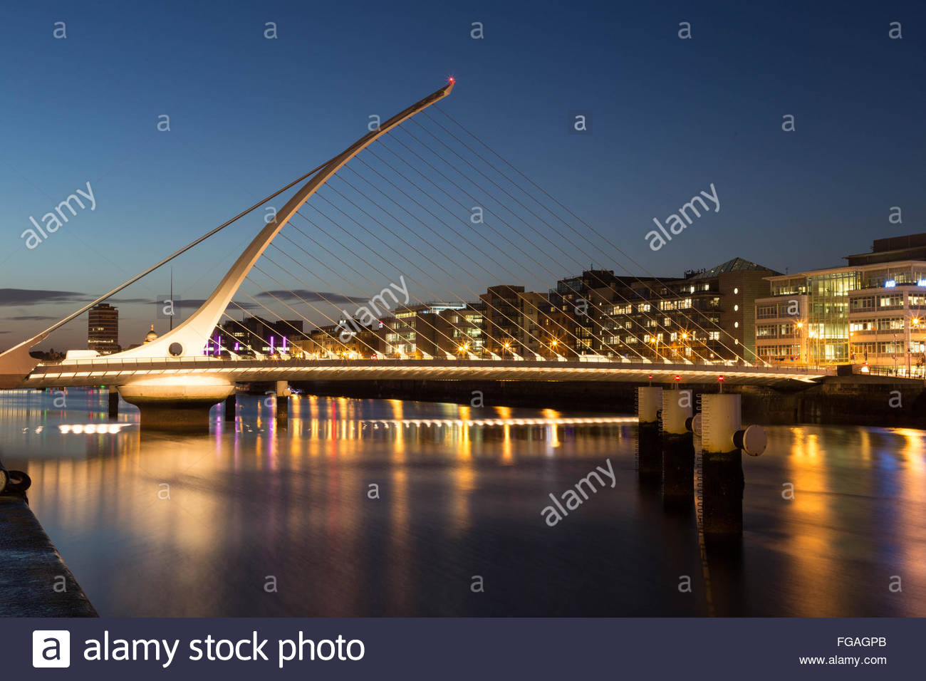 Illuminated Samuel Beckett Bridge Over River Against Sky Stock Photo