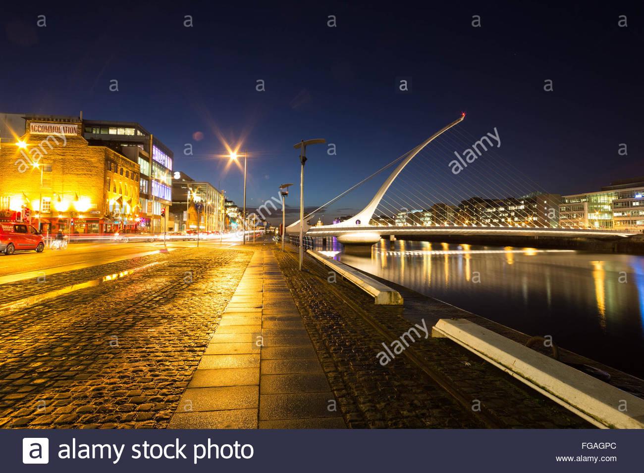 Illuminated Samuel Beckett Bridge Over River Against Sky Stock Photo